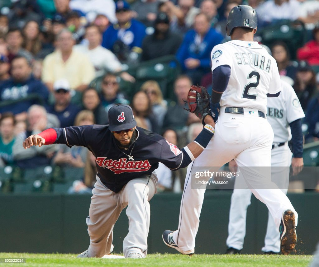 Carlos Santana #41 of the Cleveland Indians has his arm bent backwards as it catches on the hip of Jean Segura #2 of the Seattle Mariners, who was safe at first base in the fifth inning at Safeco Field on September 23, 2017 in Seattle, Washington.