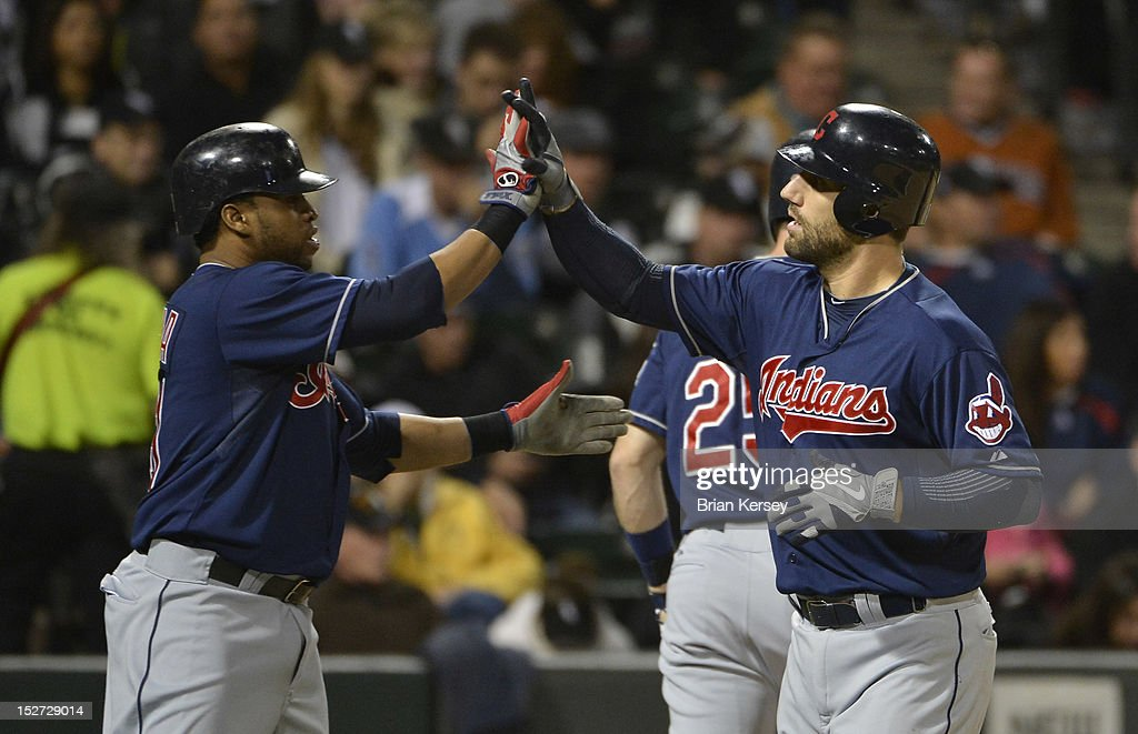 Carlos Santana #41 of the Cleveland Indians (L) high-fives teammate Russ Canzler #4 after Canzler hit a two-run home run home run scoring Santana during the sixth inning at U.S. Cellular Field on September 24, 2012 in Chicago, Illinois.