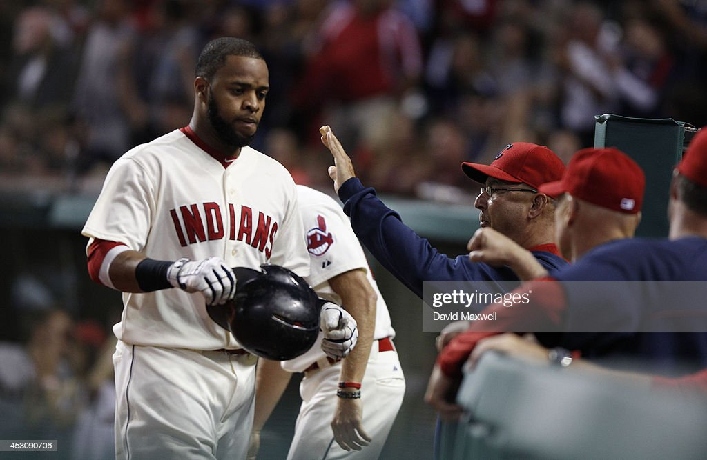 Carlos Santana #41 of the Cleveland Indians is congratulated as he returns to the dugout after scoring on a single by Nick Swisher #33 (not pictured) against the Texas Rangers during the sixth inning of their game on August 2, 2014 at Progressive Field in Cleveland, Ohio.