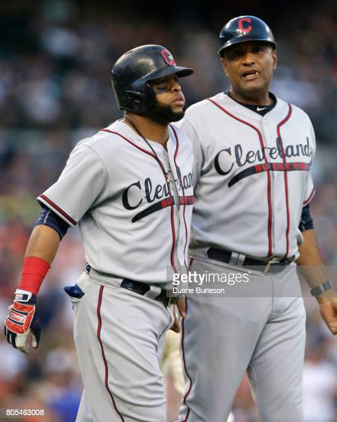 Carlos Santana of the Cleveland Indians is guided down the first base line by first base coach Sandy Alomar after the benches cleared when Santana...