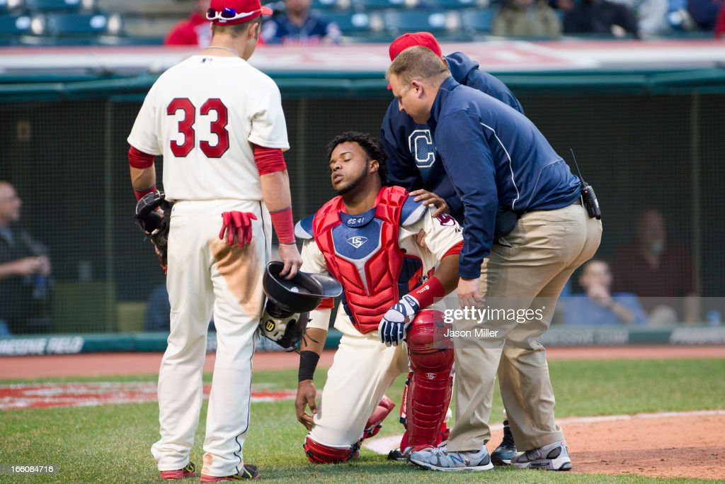 Carlos Santana #41 of the Cleveland Indians is helped up after being injured by a pitch in the ninth inning against the New York Yankees on opening day at Progressive Field on April 8, 2013 in Cleveland, Ohio. The Yankees defeated the Indians 11-6.