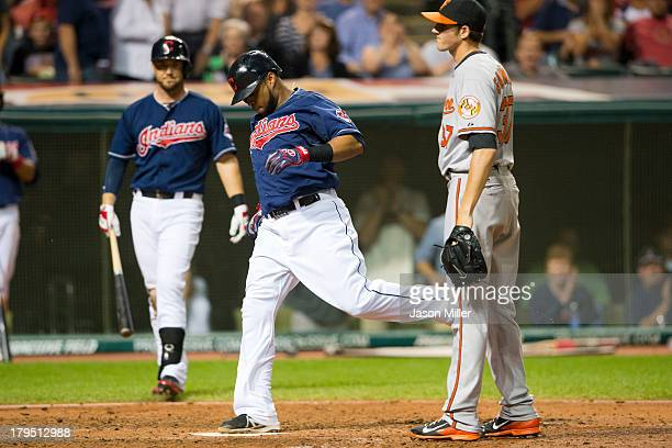 Carlos Santana of the Cleveland Indians scores on a wild pitch thrown by relief pitcher Kevin Gausman of the Baltimore Orioles during the fifth...