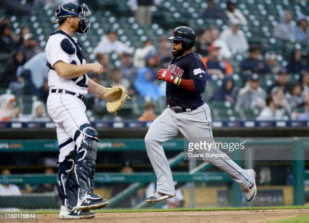 Carlos Santana of the Cleveland Indians scores past catcher John Hicks of the Detroit Tigers on a sacrifice fly ball hit by Jose Ramirez during the...