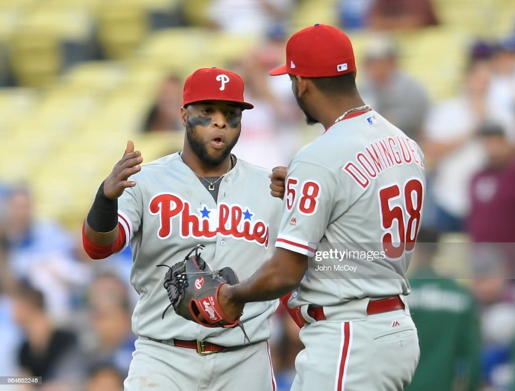 Carlos Santana #41 of the Philadelphia Phillies congratulates pitcher Seranthony Dominguez #58 after defeating the Los Angeles Dodgers 2-1 at Dodger Stadium on May 31, 2018 in Los Angeles, California.
