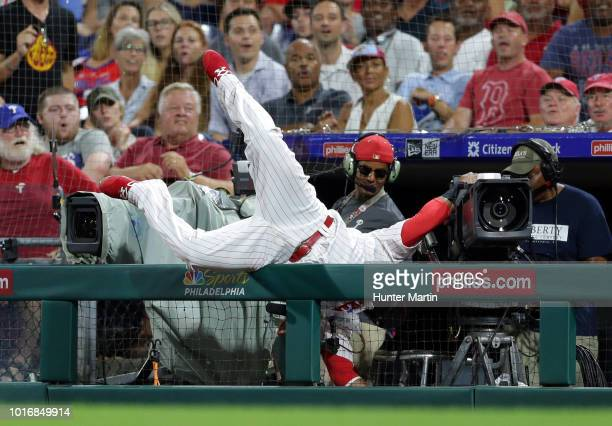 Carlos Santana of the Philadelphia Phillies falls into the television camera well attempting to catch a foul ball in the eighth inning during a game...