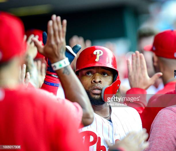 Carlos Santana of the Philadelphia Phillies high fives teammates in the dugout after hitting a threerun home run against San Diego Padres during the...