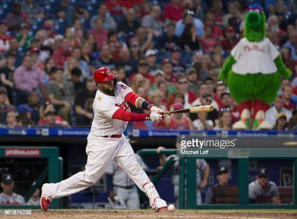 Carlos Santana of the Philadelphia Phillies hits an RBI single in the bottom of the third inning as the Phillie Phanatic looks on against the Atlanta...
