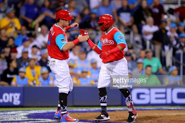 Carlos Santana of the Philadelphia Phillies is greeted by teammate Rhys Hoskins after hitting a tworun home run in the sixth inning during the 2018...
