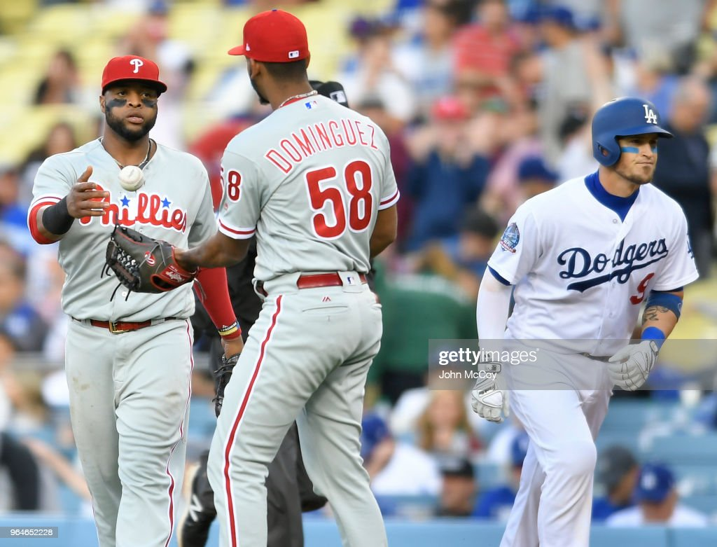 Carlos Santana #41 of the Philadelphia Phillies tosses the ball to Seranthony Dominguez #58 after Yasmani Grandal #9 of the Los Angeles Dodgers is thrown out at first for the final out of the game at Dodger Stadium on May 31, 2018 in Los Angeles, California. Philadelphia Phillies wib 2-1