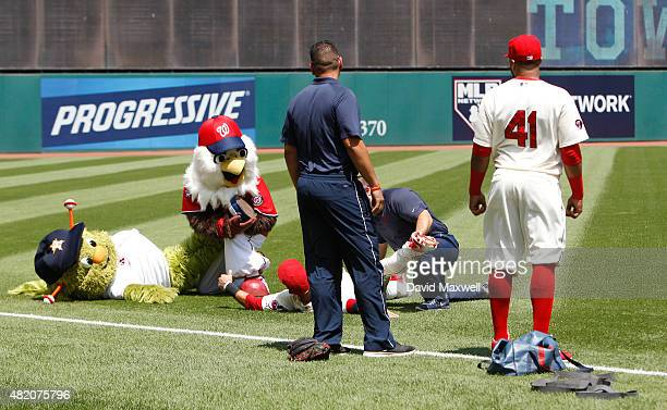 Carlos Santana the Cleveland Indians looks on as teammate Mike Aviles stretches out on the field next to MLB mascots before the start of the game...