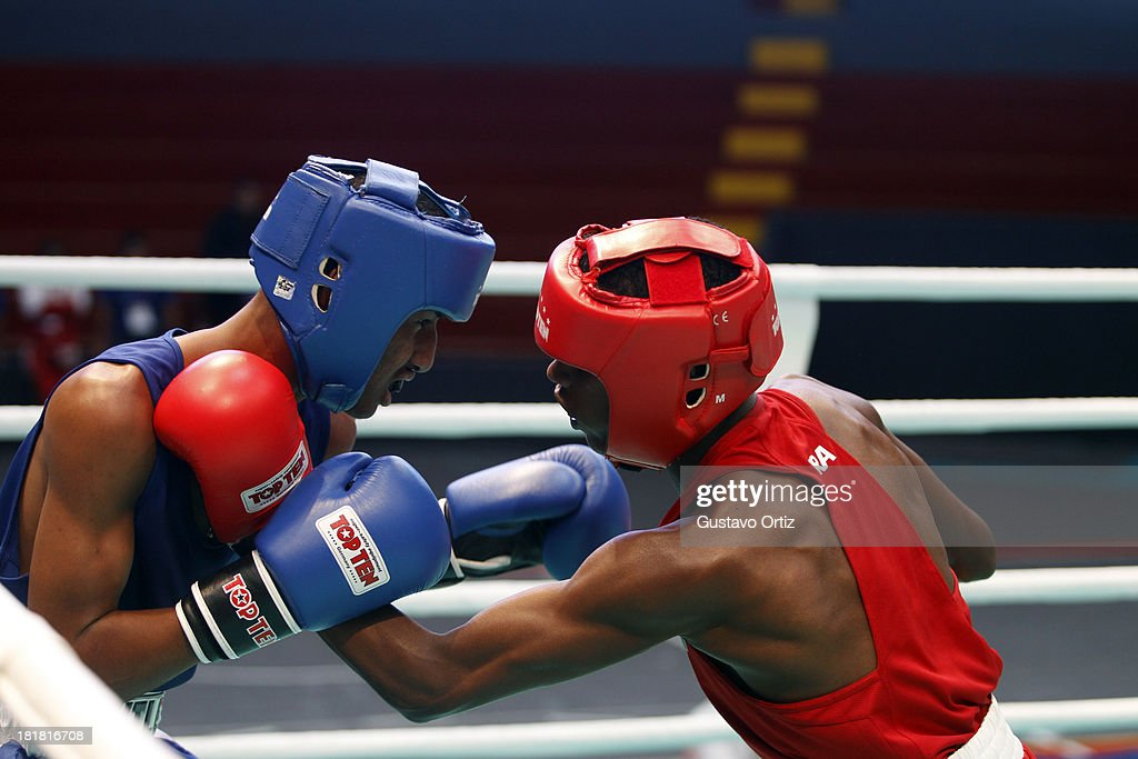 Carlos Santos of Brazil (red) fights with Jose Zarraga of Venezuela (blue) during the Men's 49kg Boxing Finals as part of the I ODESUR South American Youth Games at Coliseo Miguel Grau on September 25, 2013 in Lima, Peru.