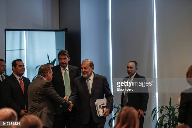 Carlos Slim chairman emeritus of America Movil SAB center shakes hands with an attendee while arriving to speak at a press conference in Mexico City...