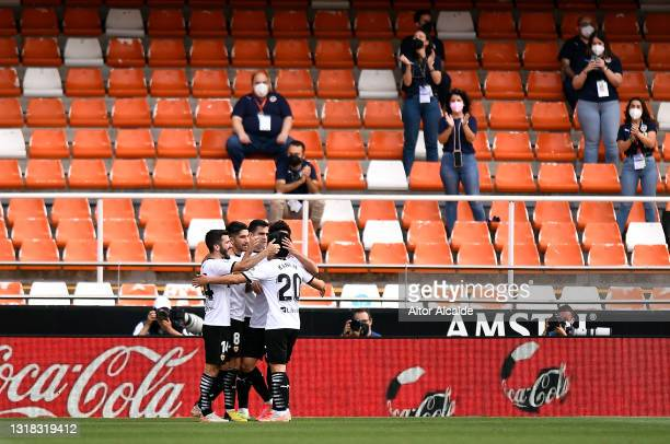 Carlos Soler of Valencia CF celebrates with team mates after scoring their side's third goal as fans wearing face masks applaud during the La Liga...