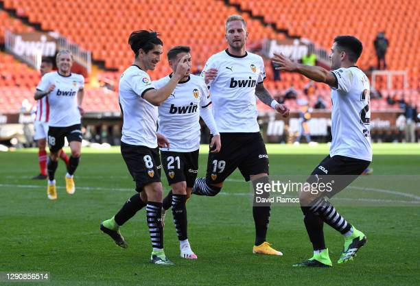 Carlos Soler of Valencia CF celebrates with teammates Manu Vallejo, Uros Racic, and Maxi Gomez after scoring his team's first goal during the La Liga...