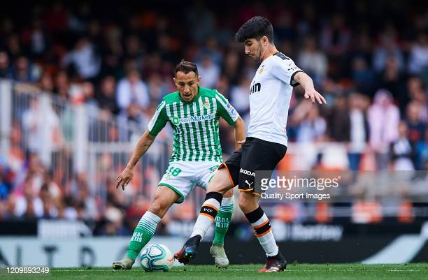 Carlos Soler of Valencia CF competes for the ball with Andres Guardado of Real Betis Balompie during the Liga match between Valencia CF and Real...