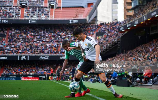 Carlos Soler of Valencia CF competes for the ball with Emerson of Real Betis Balompie during the Liga match between Valencia CF and Real Betis...
