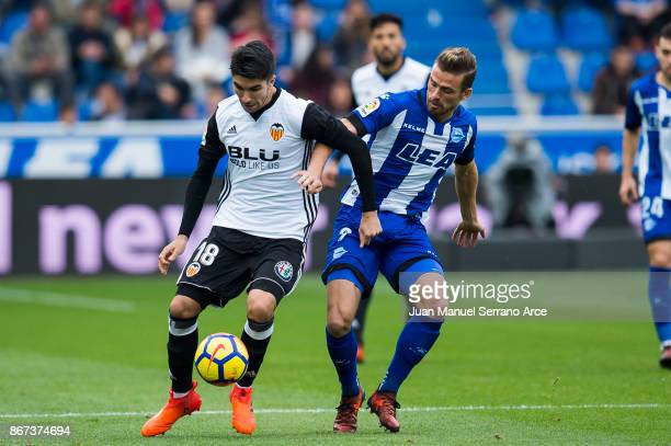 Carlos Soler of Valencia CF duels for the ball with Christian Santos of Deportivo Alaves during the La Liga match between Deportivo Alaves and...