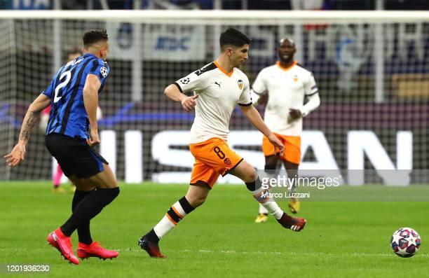Carlos Soler of Valencia CF is challenged by Rafael Toloi of Atalanta during the UEFA Champions League round of 16 first leg match between Atalanta...