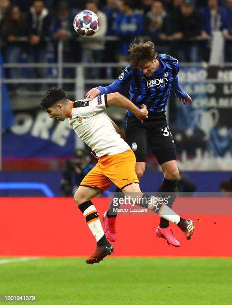 Carlos Soler of Valencia CF jumps with Hans Hateboer of Atalanta for the ball during the UEFA Champions League round of 16 first leg match between...