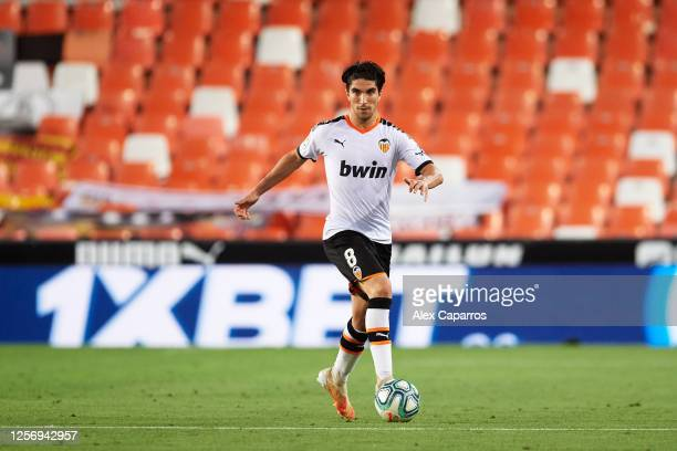 Carlos Soler of Valencia CF runs with the ball during the Liga match between Valencia CF and RCD Espanyol at Estadio Mestalla on July 16 2020 in...