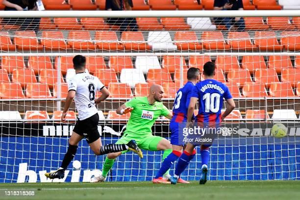 Carlos Soler of Valencia CF scores their side's second goal past Marko Dmitrovic of SD Eibar during the La Liga Santander match between Valencia CF...