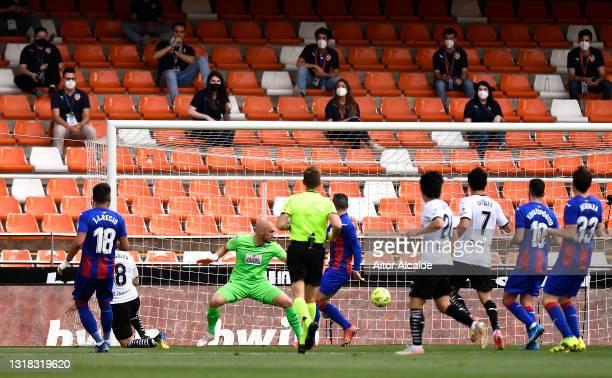 Carlos Soler of Valencia CF scores their side's third goal past Marko Dmitrovic of SD Eibar during the La Liga Santander match between Valencia CF...