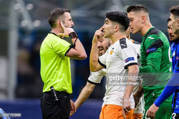 Carlos Soler of Valencia CF talks to FIFA Referee Michael Oliver of England during the UEFA Champions League round of 16 first leg match between...