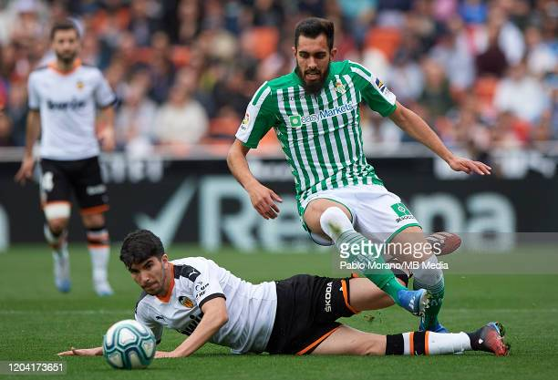 Carlos Soler of Valencia competes for the ball with Borja Iglesias of Betis during the Liga match between Valencia CF and Real Betis Balompie at...
