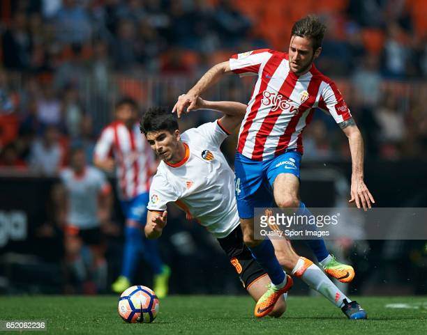 Carlos Soler of Valencia competes for the ball with Duje Cop of Real Sporting de Gijon during the La Liga match between Valencia CF and Real Sporting...