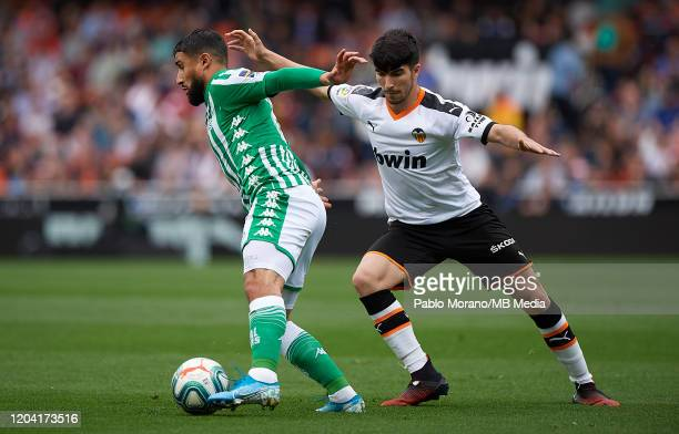 Carlos Soler of Valencia competes for the ball with Nail Fekir of Betis during the Liga match between Valencia CF and Real Betis Balompie at Estadio...