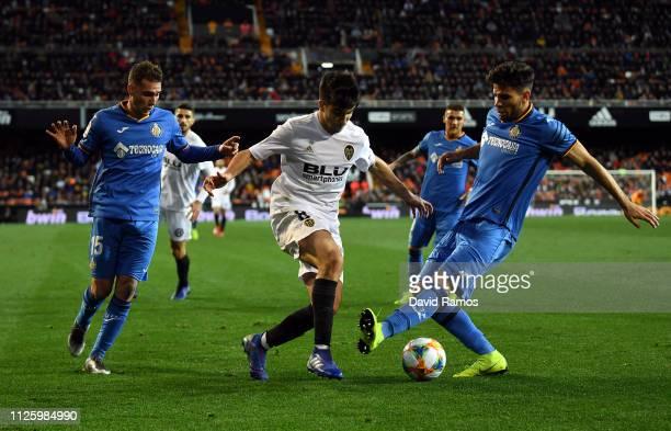 Carlos Soler of Valencia takes on Sebastian Cristoforo and Leandro Cabrera of Getafe during the Copa del Rey Quarter Final match between Valencia and...