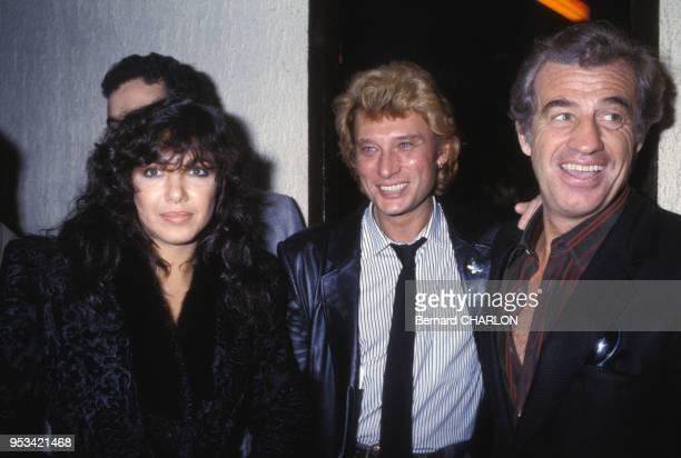 Carlos Sotto Mayor et JeanPaul Belmondo félicitent Johnny Hallyday après son concert au Palais des Sports le 11 novembre 1982 à Paris France