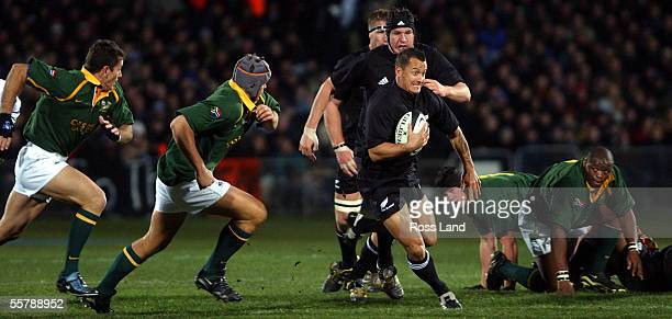 Carlos Spencer runs the ball past Juan Smith and Joost van der Westhuizen as Lawrence Sephaka and Joe van Neikerk during the All Blacks 1911 win over...