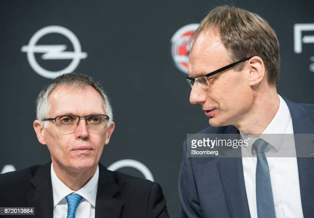 Carlos Tavares chief executive officer of PSA Group left looks on as Michael Lohscheller chief executive officer of Adam Opel AG speaks during a news...
