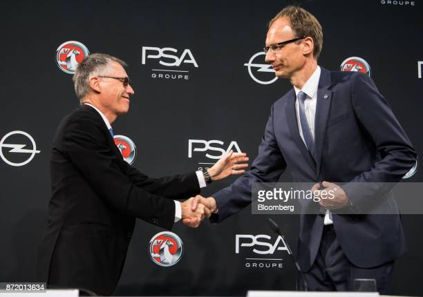 Carlos Tavares chief executive officer of PSA Group left shakes hands with Michael Lohscheller chief executive officer of Adam Opel AG during a news...
