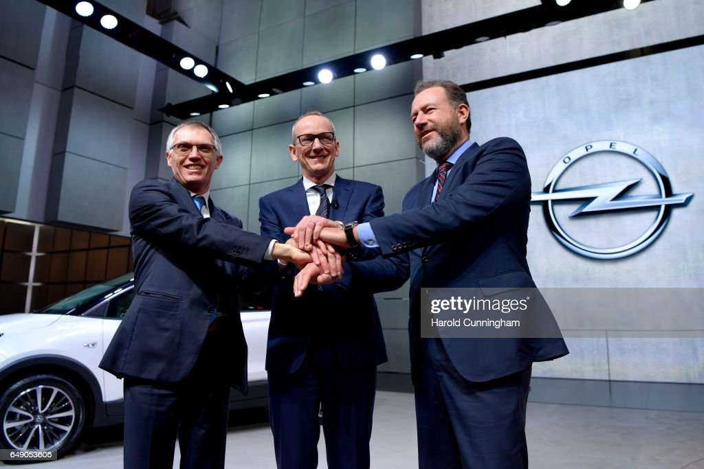 Carlos Tavares, Opel CEO Karl-Thomas Neumann and GM President Dan Ammann shake hands during the Opel press conference as part of the 87th Geneva International Motor Show on March 7, 2017 in Geneva, Switzerland. The International Motor Show showcases new models from the car industry.
