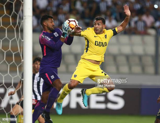 Carlos Tevez Boca Juniors struggles for the ball with Daniel Prieto goalkeeper of Alianza Lima during a groups stage match between Alianza Lima and...