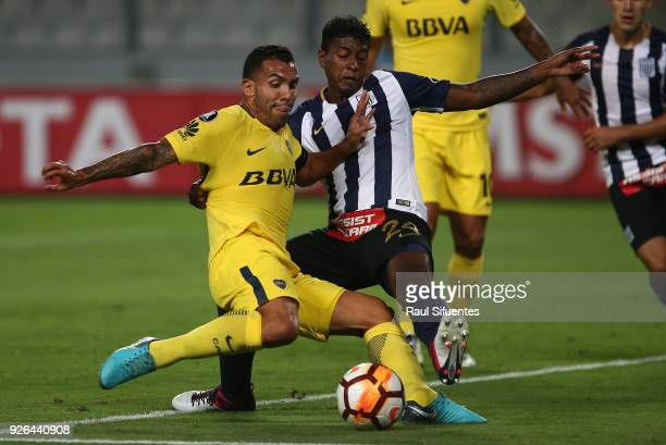 Carlos Tevez Boca Juniors struggles for the ball with Miguel Araujo of Alianza Lima during a groups stage match between Alianza Lima and Boca Juniors...