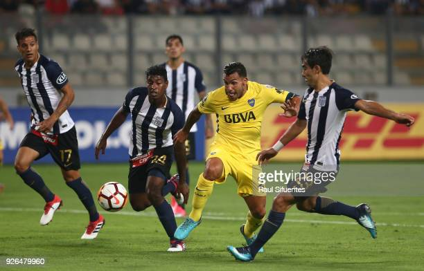 Carlos Tevez Boca Juniors struggles for the ball with Miguel Araujo and Marco Garro of Alianza Lima during a groups stage match between Alianza Lima...