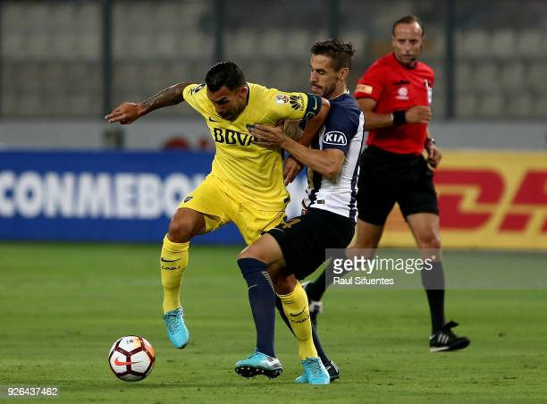 Carlos Tevez Boca Juniors struggles for the ball with Tomas Costa of Alianza Lima during a groups stage match between Alianza Lima and Boca Juniors...