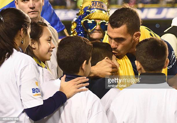 Carlos Tevez kisses a child during his presentation as new player of Boca Juniors at Alberto J Armando Stadium on July 13 2015 in Buenos Aires...