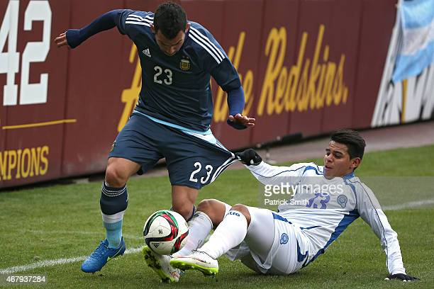 Carlos Tevez of Argentina dribbles past Alexander Larin of El Salvador in the first half during an International Friendly at FedExField on March 28...