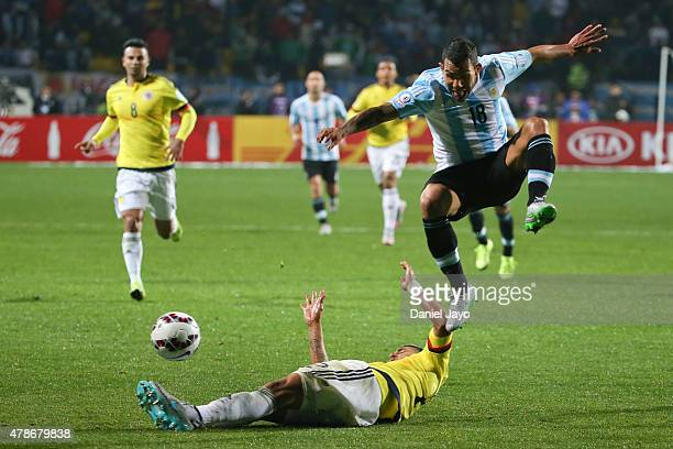 Carlos Tevez of Argentina jumps over Jeison Murillo of Colombia during the 2015 Copa America Chile quarter final match between Argentina and Colombia...