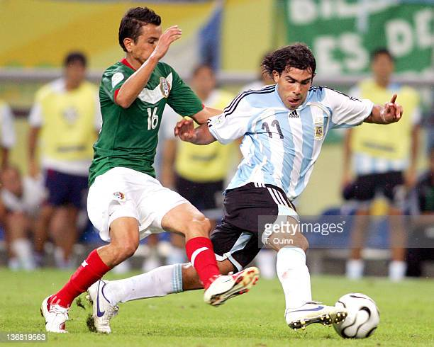 Carlos Tevez of Argentina moves the ball away from Mario Mendez of Mexico during the Round of 16 match at Zentralstadion in Leipzig Germany on June...