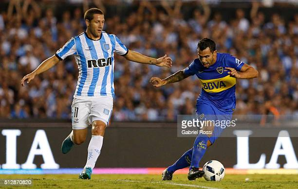 Carlos Tevez of Boca Juniors battles for the ball with Luciano Aued of Racing Club during a fifth round match between Racing Club and Boca Juniors as...