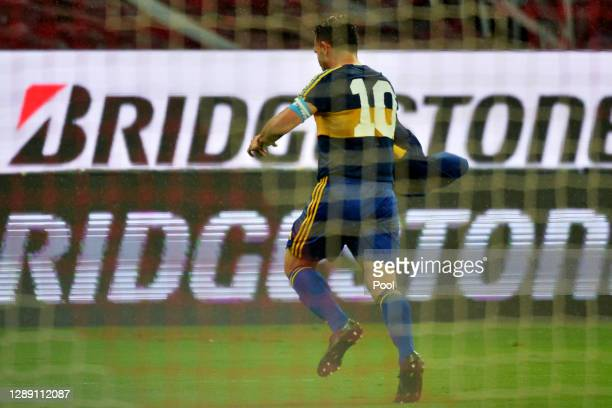 Carlos Tevez of Boca Juniors celebrates after scoring the first goal of his team wearing a vintage jersey of Boca Juniors in tribute to the late...