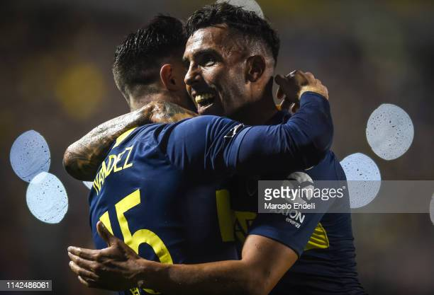 Carlos Tevez of Boca Juniors celebrates after scoring the second goal of his team with teammate Nahitan Nández during a group G match between Boca...