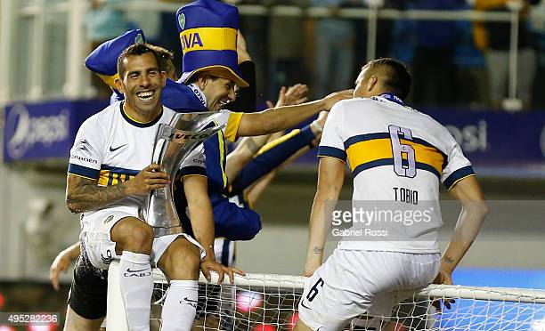 Carlos Tevez of Boca Juniors celebrates after winning the local soccer tournament holding the trophy after a match between Boca Juniors and Tigre as...