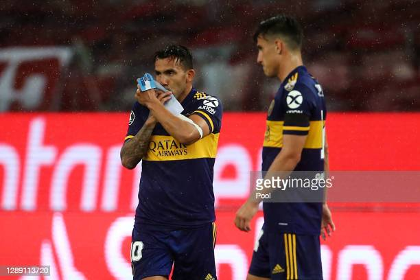 Carlos Tevez of Boca Juniors celebrates with teammates after scoring the first goal of his team during a round of sixteen first leg match between...