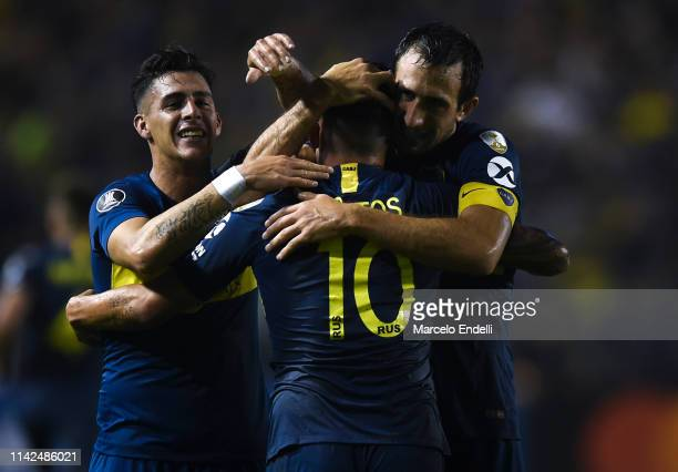 Carlos Tevez of Boca Juniors celebrates with teammates Cristian Pavón and Carlos Izquierdoz after scoring the second goal of his team during a group...